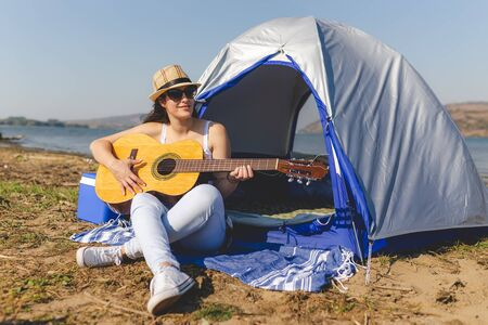 Young female sitting in front of tent and playing acoustic guitar. Music, freedom and nature concept. Banco de Imagens - 133493854