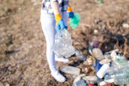 Close up of volunteer holding plastic bottle trash outdoors. Environment and save the earth concept. Banco de Imagens