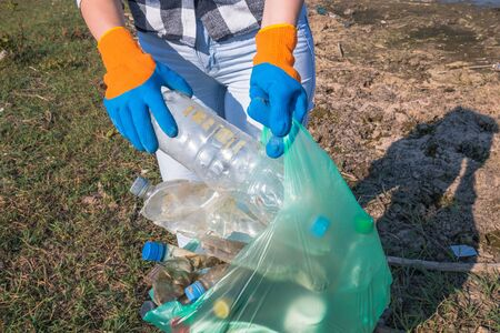 Female volunteer picking up plastic trash outdoors. Environment and save the earth concept. Banco de Imagens