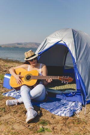 Woman tourist with guitar sitting next to tent. Banco de Imagens