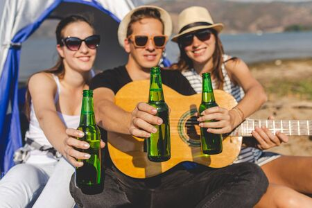 Guitar player with his friends showing bottles of beer while having a great time during camping at the beach. Banco de Imagens - 133493856
