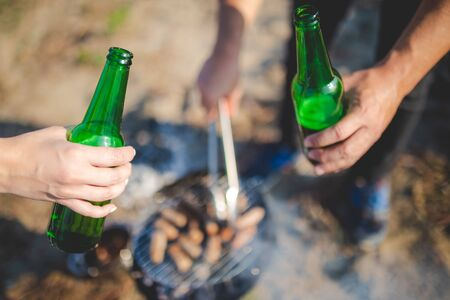 Friends clinking bottles of beer while preparing kebab lunch on barbecue grill outdoors.