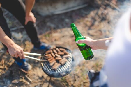 Close up of people holding beer bottle and preparing kebabs on barbecue grill. Food preparation on camping or picnic concept.