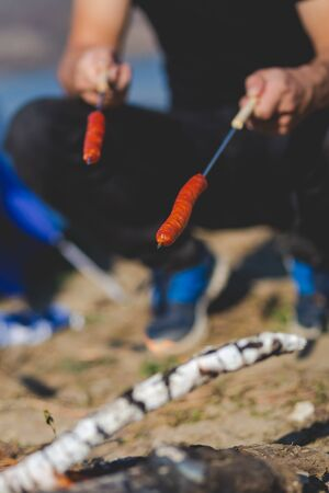 Camping in the wild - Grilled sausages impaled on a stick above the campfire.