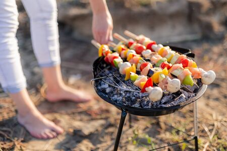 Woman hand turning meat and vegetables while grilling on barbecue. Picnic or camping food concept.