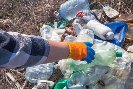 Close up of woman hand collecting plastic garbage. Recycling and ecology concept.