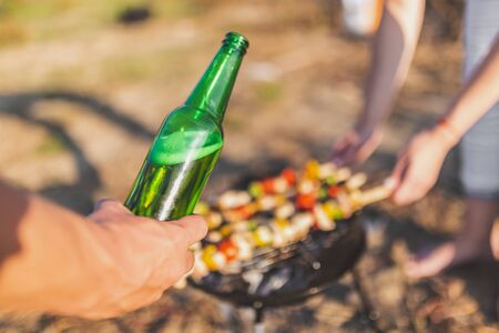 Close up of man hand holding beer bottle over barbecue grill. Food preparation on camping or picnic concept.