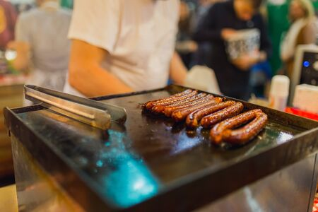 Close up image of sausages cooking on a flat grill. Street food concept.