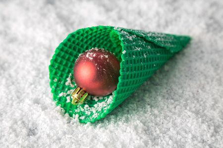 Close up of ice cream cone with Christmas decoration bauble on snow minimal creative holiday concept.