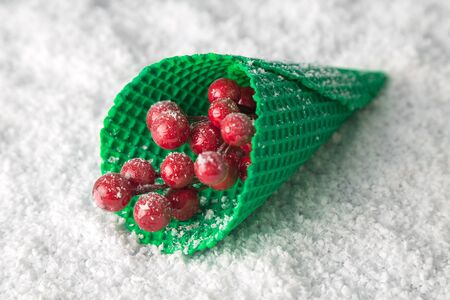 Close up of ice cream cone with Christmas red berries on snow minimal creative holiday concept.