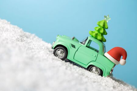 Retro car toy with Christmas tree and Santa hat driving up the snowy mountain minimal creative winter holiday concept. Banco de Imagens