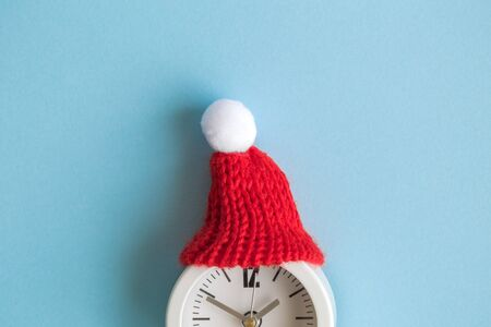 Flat lay of white alarm clock wearing red winter hat against pastel blue background minimal creative christmas holiday concept. Space for copy. Banco de Imagens
