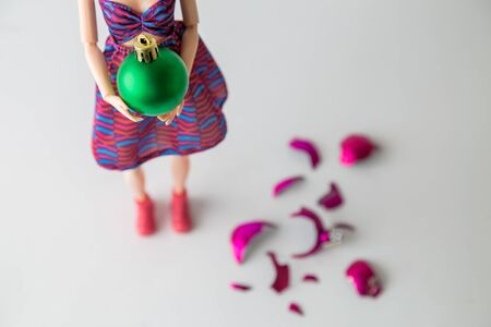 Close up of female doll holding Christmas bauble next to broken one on the floor minimal creative holiday concept.
