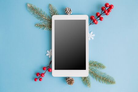 Flat lay of blank screen digital tablet with christmas tree branches, snowflakes and red berries on pastel blue background minimal creative holiday concept. Banco de Imagens