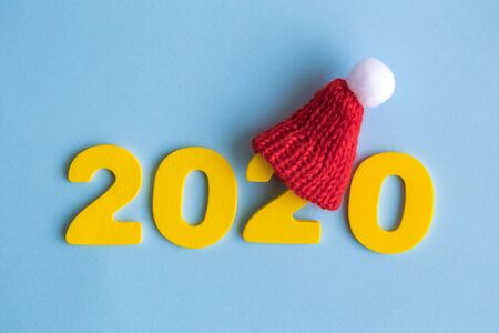 New year concept 2020 made of wooden numbers and red winter hat on pastel blue background.