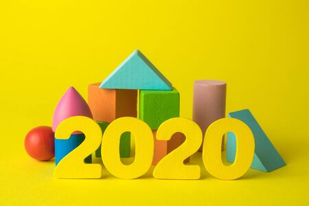Creative background made of wooden 2020 numbers and colorful geometric shapes on yellow minimal new year concept.
