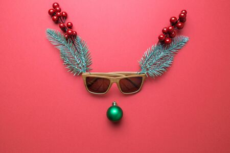 Reindeer face made of Christmas decorations, sunglasses, holly berries and pine branches. Minimal concept. Flat lay
