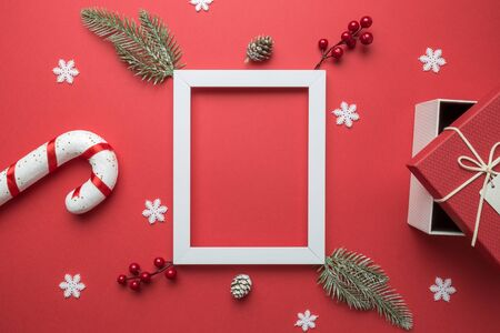 Flat lay of photo frame with christmas composition decoration on red background. Space for copy. Banco de Imagens
