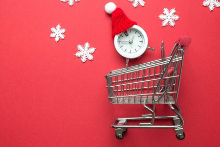 Time for Christmas shopping composition made of shopping cart, alarm clock with hat and snowflakes. Space for copy.