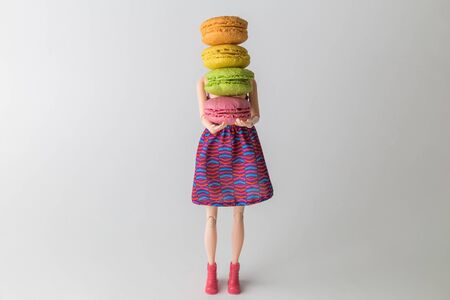 Girl doll holding colorful macaroons minimal creative sweet food concept.