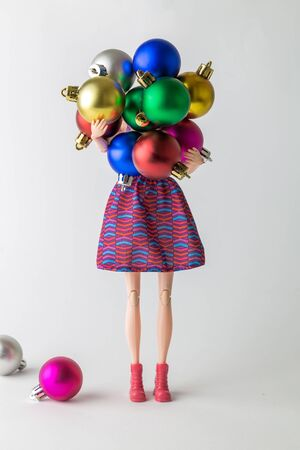 Christmas or new year abstract made of doll carrying multicolored decoration balls winter holidays concept.
