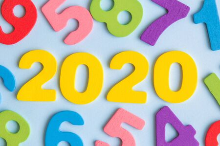 New year concept 2020 made of wooden numbers on pastel blue background.