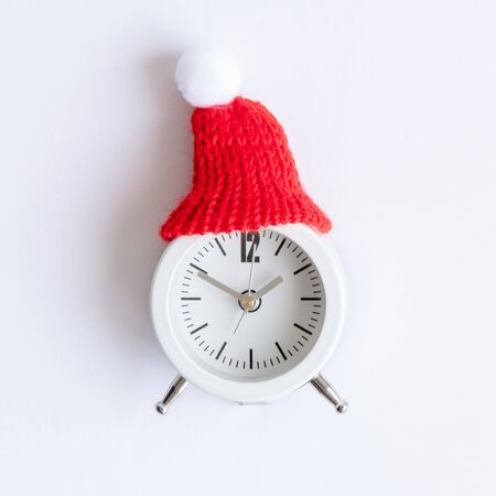 Flat lay of white alarm clock wearing red winter hat against white background minimal creative christmas holiday concept.