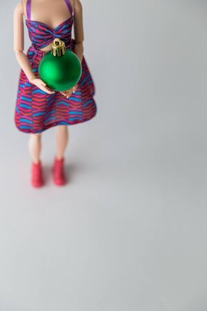 Close up of female doll holding green Christmas bauble minimal creative holiday concept.