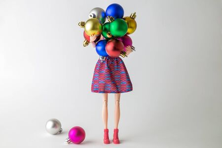 Girl doll holding colorful baubles and preparing for Christmas home decoration minimal creative holiday concept.
