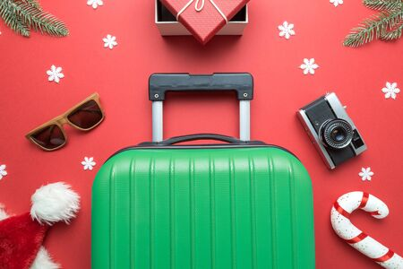 Christmas holiday minimal creative composition made of suitcase, gift box, sunglasses,Santa hat, candy cane, retro photo camera, fir branches and snowflakes on red background.