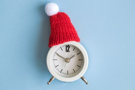 Small analog clock with hat abstract. Winter season and christmas time concept.