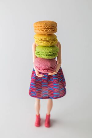 Food abstract made of doll carrying multicolored macaron cookies dessert.