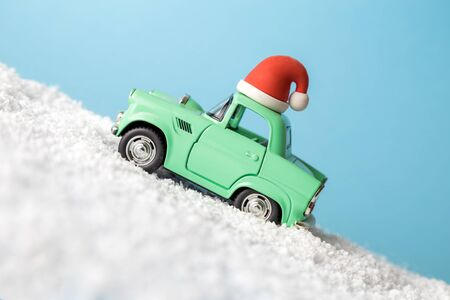Side view of small car with Christmas holiday equipment driving through snow abstract. Banco de Imagens
