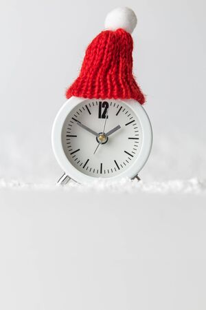 Small analog clock with hat in snow abstract. Winter season and christmas time concept. Space for copy. Banco de Imagens
