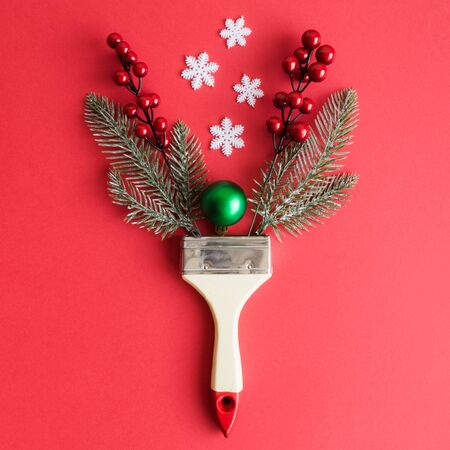 Paint brush with christmas decoration abstract on red background.
