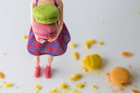Girl doll holding colorful macaroons and broken ones on the floor minimal creative sweet food concept.