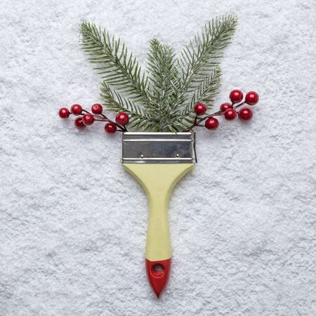 Flat lay of paint brush with christmas tree branches and red berries on snow minimal creative holiday concept. Banco de Imagens