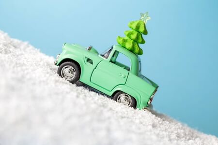 Retro car toy with Christmas tree driving up the snowy mountain minimal creative winter holiday concept.