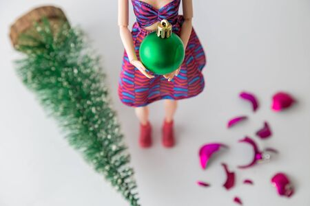 Close up of female doll holding Christmas bauble next to broken one on the floor and knocked down fir tree minimal creative holiday concept. Banco de Imagens