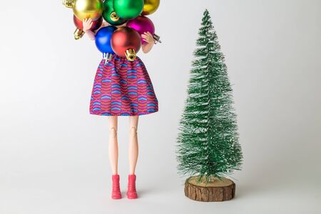 Girl doll holding colorful baubles next to fir tree and preparing for Christmas home decoration minimal creative holiday concept.