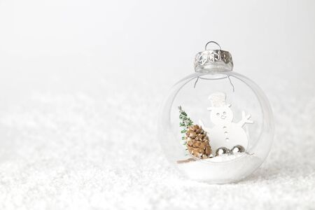 Creative layout of Christmas bauble decoration with snowman, pine cone, fir tree and bells on snow. Holiday background. Space for copy.