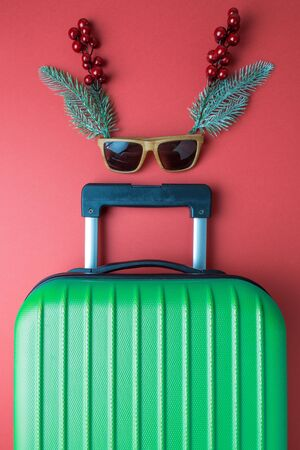 Flat lay of suitcase with reindeer face made of sunglasses and fir tree branches with holly berries on red background minimal creative christmas travel concept.