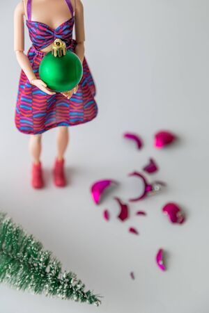 Top view of fashionable doll with Christmas decoration ball. Pink shattered bauble and christmas tree on the floor. Banco de Imagens