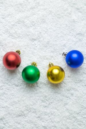 Creative layout of colorful Christmas baubles decoration on snow. Holiday background. Space for copy.