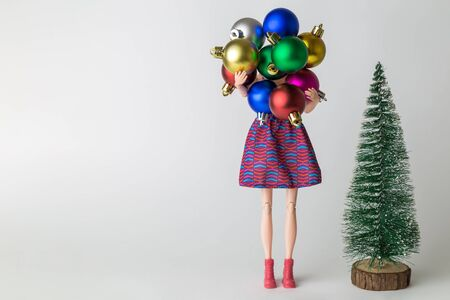Winter holidays abstract made of Christmas tree and doll carrying multicolored decoration balls
