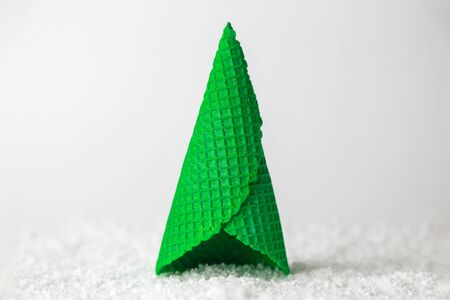 Ice cream cone in form of christmas tree on snow minimal creative holiday concept.