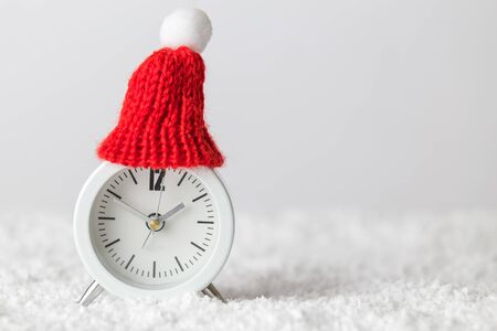 White alarm clock wearing red winter hat in snow minimal creative christmas holiday concept.