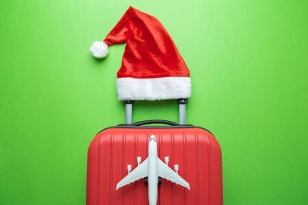 Flat lay of luggage with red santa hat and small commercial aircraft abstract on green.