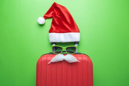 Santa Claus abstract made of suitcase, Santa hat, sunglasses and white mustache minimal creative Christmas travel concept. Banco de Imagens