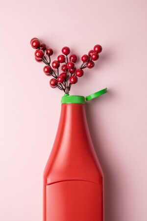 Flat lay of plastic ketchup bottle and red berries or cherry tomatoes plant on pastel pink background abstract.